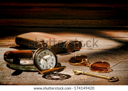 American West frontier traveler vintage travel items with antique pocket watch and cigar on  ashtray with ancient sunglasses and room key on a wood table in old western hotel during traveling stay