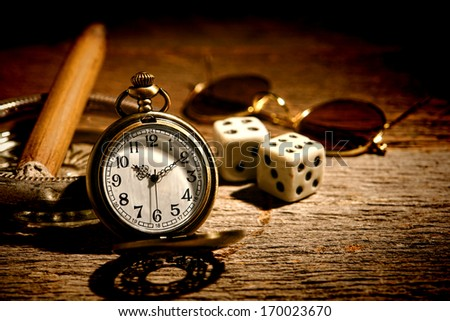 American West legend antique pocket watch with gambler craps dice and cigar in an old ashtray waiting on a vintage western saloon wood table ready for gambling and cheating at a game - stock photo