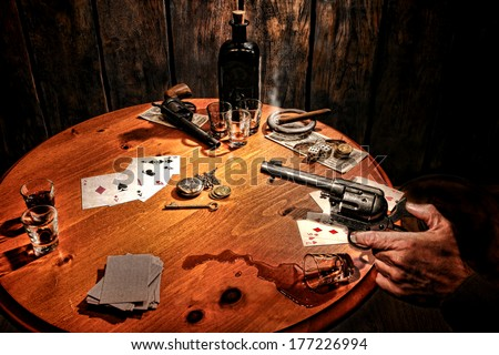 American West Legend armed gambler bandit holding revolver gun in hand and threatening cheater cowboy after poker cards game incident with cheating and drinking in an old western gambling saloon scene - stock photo