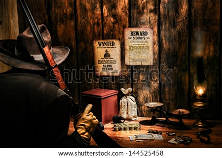 American West Legend armed security guard with rifle and cowboy hat guarding western railroad payroll and revenue office with gold coins and vintage money with strongbox and bag on paymaster old desk - stock photo