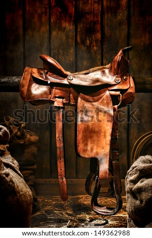 American West legend authentic rodeo cowboy used and worn brown leather western saddle on a wood rail in an old ranch wood barn