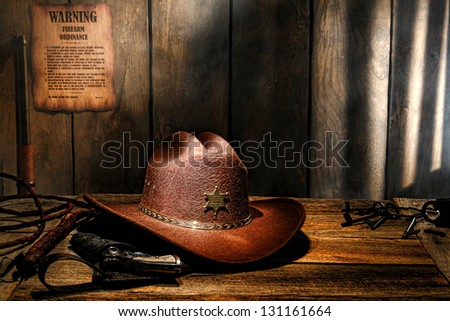 American West legend brown felt western cowboy hat on aged wood table sheriff desk with old lawman gun in holster and bullwhip in a dark county jail - stock photo
