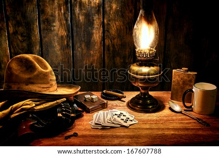 American west legend cowboy  hat  and gun in holster on  old Western hotel room  nightstand table with vintage poker playing cards and  kerosene oil lamp  everyday  items in  nostalgic Americana scene
