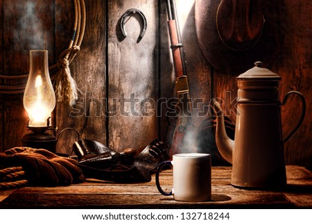 American West legend cup of hot steamy coffee and brewing pot on an old wood table with traditional cowboy gear and aged tools in an antique western wooden cabin on a ranch - stock photo