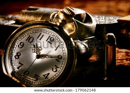 American West Legend outlaw antique pocket watch keeping time and leaning against a loaded bandit revolver gun with an assassin bullet ready for a gunslinger western frontier gunfight  - stock photo