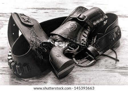 American West legend revolver style old six-shooter gun in antique cowboy leather holster on grunge aged wood planks