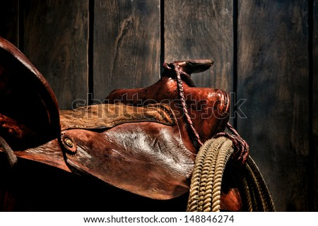 American West Legend rodeo cowboy roping lariat lasso hanging on an authentic used and worn brown leather western saddle in an old ranch barn - stock photo