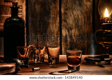 American West legend whisky shot glass drink with empty glasses and vintage whiskey bottle on antique wood bar counter with cowboy revolver gun in an antique frontier saloon scene lit by dim oil lamp - stock photo