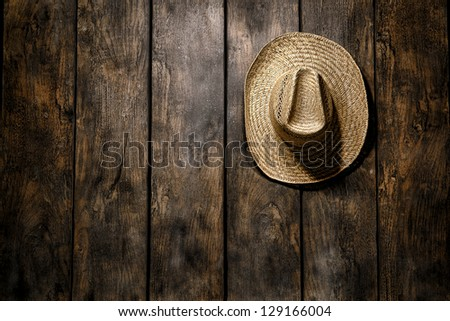 American West rodeo country farmer traditional straw hat hanging on distressed wood boards wall in a vintage ranch barn - stock photo