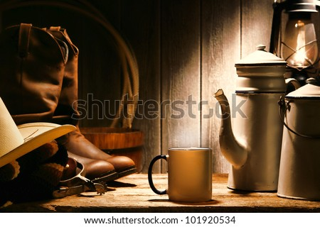 American West rodeo cowboy authentic working gear with genuine hat and leather rancher boots on an old wood table with vintage cup and steel enamel pot of coffee for a break in an antique ranch barn - stock photo