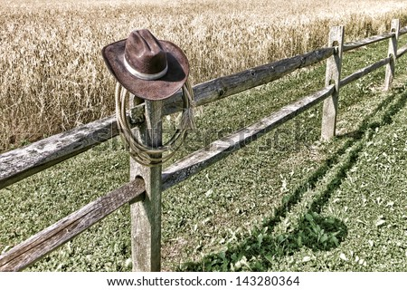 American West rodeo cowboy brown hat and roping lasso lariat hanging on an old wood fence post on a western ranch field - stock photo
