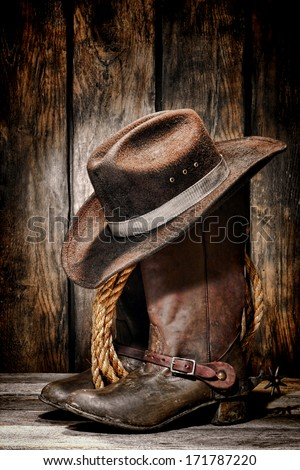 American West rodeo cowboy dirty and used black felt hat atop worn and old leather working rancher boots with vintage spurs and ranching rope in an antique ranch barn