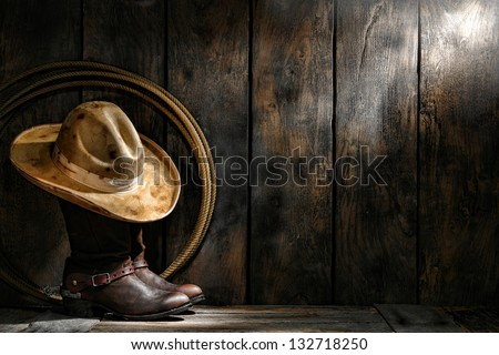 American West rodeo cowboy dirty used felt hat atop worn leather working rancher roper boots with old spurs and lasso lariat in an antique ranch weathered wood cabin - stock photo