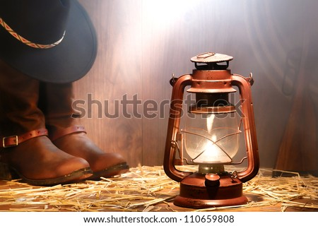American West rodeo cowboy gear with hat atop authentic leather roping boots and lasso lariat with antique shotgun lit by a vintage kerosene lantern lamp and soft light in smoke in old ranch wood barn - stock photo