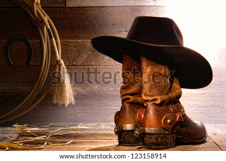 American West rodeo cowboy traditional black felt hat resting on worn leather working rancher roper boots with authentic Western riding spurs and lasso lariat in a vintage ranch wood barn - stock photo