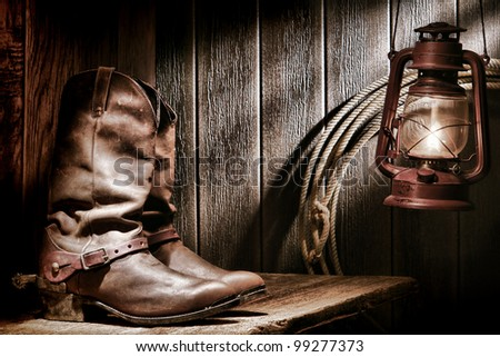 American West rodeo cowboy traditional leather roper boots with authentic Western riding spurs on an old wood bench in a vintage ranch barn lit by a nostalgic kerosene oil lamp