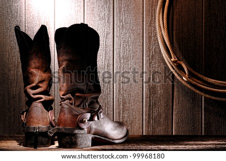 American West rodeo cowboy traditional leather slouch boots rear heel view with roping riding spurs from back and authentic Western lasso lariat hanging on weathered wall in an old wood barn - stock photo