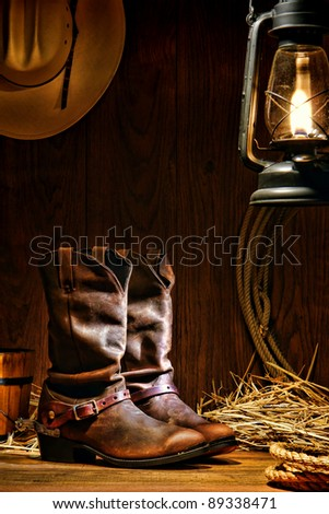 American West rodeo cowboy traditional leather working roper boots with authentic Western riding spurs in a vintage ranch barn with ranching tools lit by an old nostalgic kerosene oil lantern