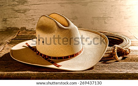 American West rodeo cowboy traditional white straw hat on an old wood table in an antique western rancher barn lit by soft diffused Laredo morning light - stock photo