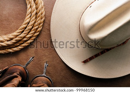 American West rodeo cowboy traditional white straw hat with roping lasso rope and vintage western riding spurs on brown leather boots over hide background - stock photo