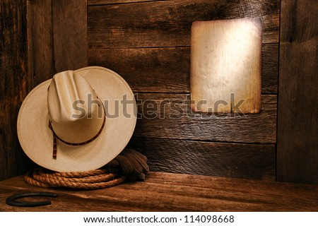 American West rodeo cowboy white straw hat and authentic western rope lasso on weathered wood floor in an old ranch barn with aged antique poster notice on wall - stock photo