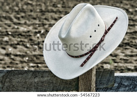 American West rodeo cowboy white straw hat on an old wood fence post on an agriculture farm field at a Western ranch   - stock photo