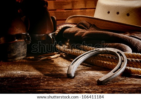 American West rodeo old horseshoe on lariat lasso and roping work gloves with Western horse rider gear with hat and aged leather roper boots on antique wood boars in a ranch barn - stock photo