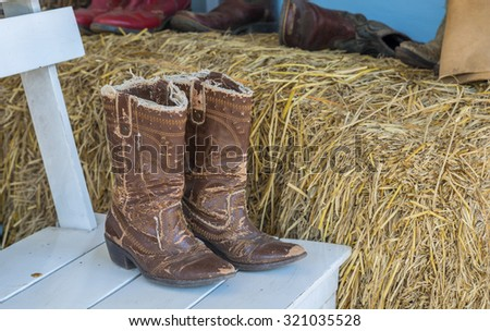 American West rodeo pair of traditional leather roper style western riding slouch cowboy boots with authentic ranching spurs on white wood chair near rick in front of an old ranch . - stock photo