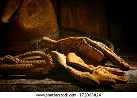 American West rodeo tough leather ranching gloves on authentic lasso lariat with vintage western cowboy hat in on old ranch barn weathered wood table - stock photo