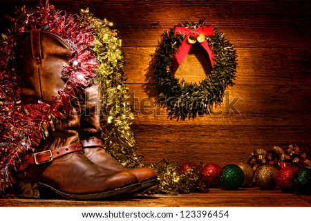 American West rodeo traditional leather cowboy boots in vintage wood cabin with festive merry Christmas display decoration in authentic country western decor for nostalgic Christmastime greeting card - stock photo
