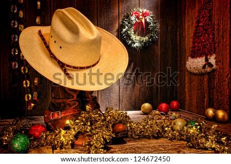 American West rodeo traditional white straw cowboy hat atop rancher boots with festive Christmas display decoration in authentic country wood barn for a nostalgic Western Christmastime greeting card - stock photo