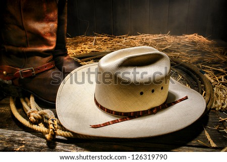 American West rodeo traditional white straw cowboy hat on an authentic Western lariat lasso with roper leather boots on wood floor in a ranch barn - stock photo