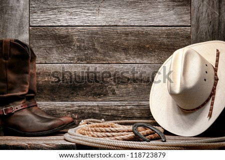 American West rodeo traditional white straw cowboy hat with authentic Western lariat lasso and roper leather boots on distressed barn wood background