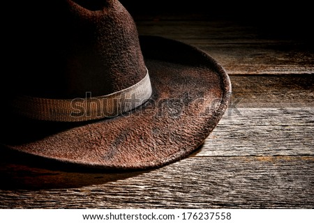 American west rodeo used and worn brown felt hat with old dirty fabric band on weathered wood planks in a western ranch wooden barn - stock photo