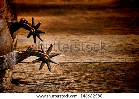 American West rodeo vintage riding spurs with sharp spikes rowel on authentic western cowboy traditional leather boots on old aged wood background in an antique ranching barn - stock photo