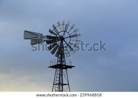 American windmill and a sky with different clouds. - stock photo