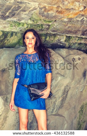 American Woman Summer Casual Fashion in New York. Beautiful lady with long black hair, wearing  blue dress, belt, holding leather purse, standing by rocks at park, relaxing. Instagram filtered effect. - stock photo