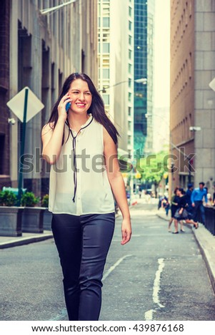 American Woman traveling in New York in summer, wearing white collarless sleeveless shirt, black pants, walking on vintage narrow street, talking on cell phone, smiling. Instagram filtered effect.