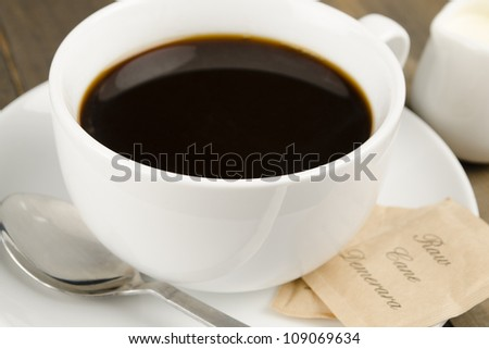 Americano black coffee in a white cup with raw demerara sugar sachets and a jug of milk. - stock photo