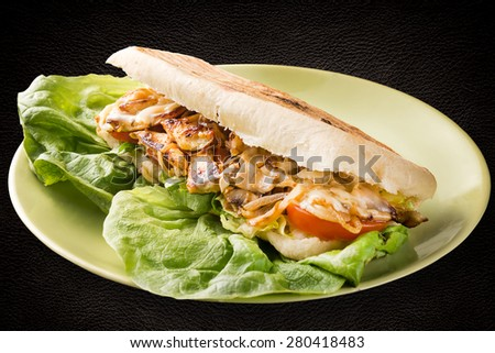 Americano - ciabatta, chicken breast, mushrooms, onions and melted cheese on dark background
