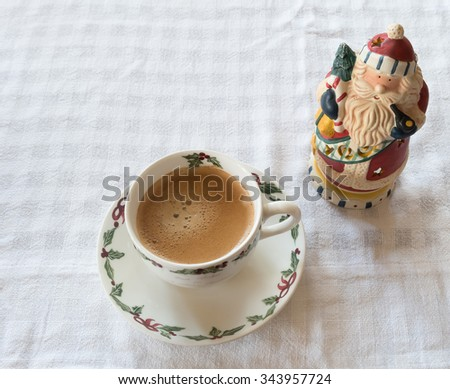 Americano coffee in christmas cup and santa claus candle holder on scott fabric. - stock photo