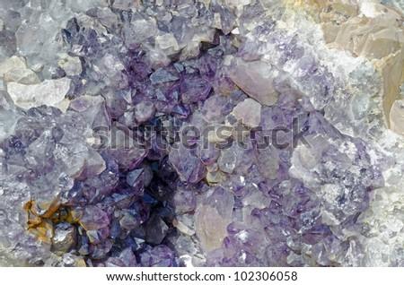 Amethyst druse over beige rock - stock photo