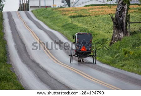 Amish buggy traveling up a road in rural Lancaster County Pennsylvania. - stock photo