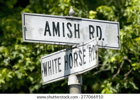 Amish horse and carriage driving past barn in Lancaster County, Pennsylvania - stock photo