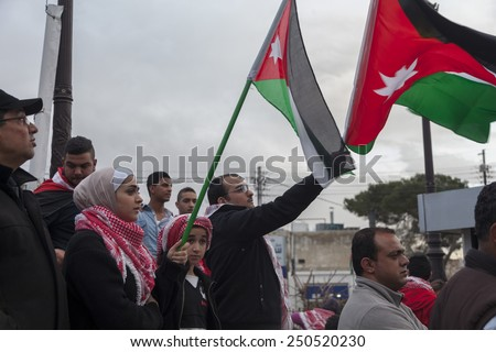 AMMAN/JORDAN - FEB 06 2015: People wave Jordanian flags at a gathering in memory of Jordanian fighter pilot, who was burnt alive by ISIS militants in Syria.
