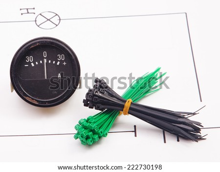 Ammeter and plastic ties on a background of the electric scheme - stock photo