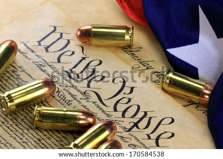 Ammunition and American flag on US Constitution - History of the Second Amendment - stock photo