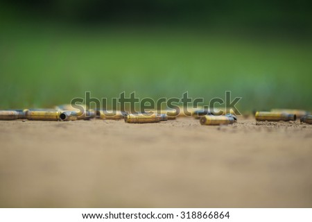 Ammunition , short of ammunition , a rifle shell casings , old and new , in box , on the prairie landscape timber .  - stock photo