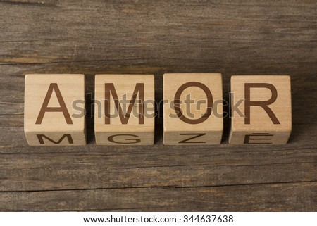 AMOR text on a wooden background - stock photo