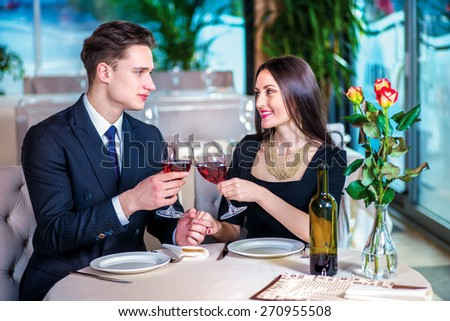 Amorous Celebratory supper for two. Romantic dinner in the restaurant. Young loving couple visits a restaurant and raised their glasses of wine while the guy holding the hand of a woman - stock photo